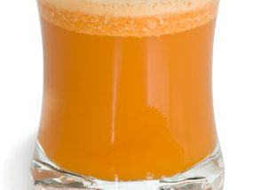 A glass of fresh raw carrot juice. Isolated with work path.