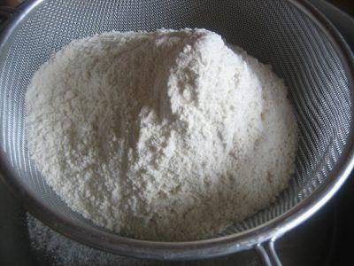 Tamizando la harina para hacer la pizza