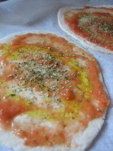 Pizza con aceite, tomate, sal y oregano. Lista para meter en el horno